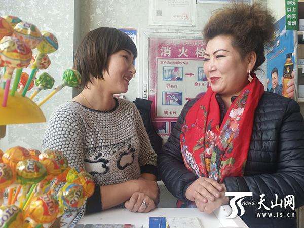 阿依木尼沙(右)在阿吉姑丽 · 阿山的超市里和她座谈。