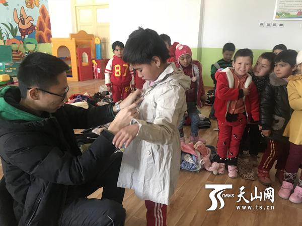 支教先生张子扬在为米炎班古丽 · 艾海挑试衣服。
