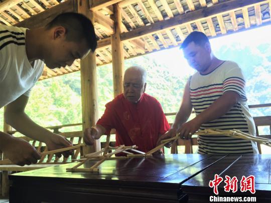 图为黄春财与儿子、孙子共同演示木拱廊桥搭建。 叶茂 摄