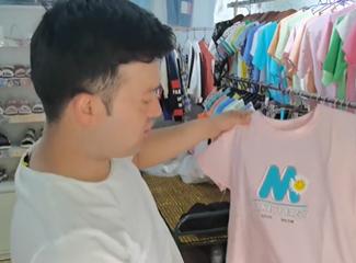 依尔帕尼介绍他家店里的小孩子穿的T恤